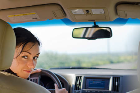 Woman driver looking over the back of the drivers seat into the rear of the car breaking her concentration on the road Stock Photo - 14826307