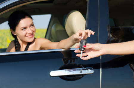 passing over: Smiling driver holding her car key out of the window of the vehicle towards a second womans outstretched hand