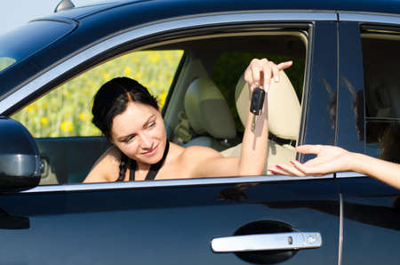 Beautiful woman driver being handed her car keys through the open car window by a female hand photo