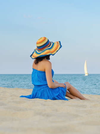 Woman with a colorful hat relaxing on sandy beach by the sea photo