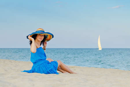 Attractive woman in blue dress sitting by the sea on beautiful sandy beach Stock Photo - 14839178