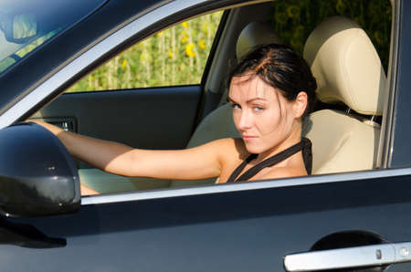Guilty looking female driver with no seatbelt looking up through the open window of her car Stock Photo - 14840901