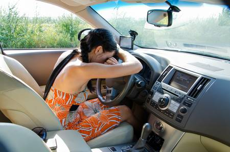 Exhausted young woman driver resting her head on her arms on the steering wheel photo
