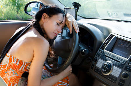 Tired woman driver taking a refreshing nap leaning on the steering wheel of the car before resuming her journey