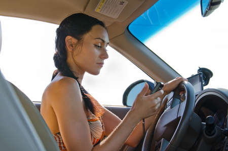 Woman driver sitting behind the steering wheel reading a text message on a mobile photo