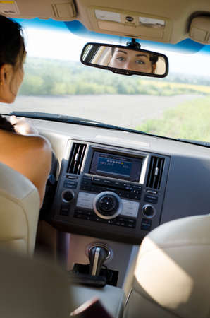 View from the back of the vehicle of a woman driver looking in her rear view mirror