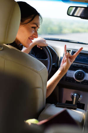 View from the back seat of a woman driver giving a heavy metal horns sign as she looks at someone in the passenger seat photo