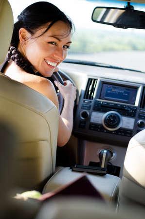 Glimlachend vrouwelijke bestuurder kijkt over haar schouder naar de achterbank van de auto