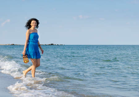 Happy woman in a blue summer dress holding her sandals in her hand splashing through the surf at the seaside with copyspace photo