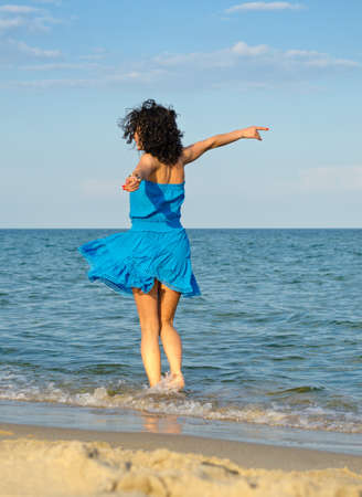 outspread: Carefree woman dancing in the sea with her arms outspread Stock Photo