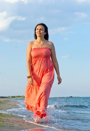 Attractive middle-aged woman in a long orange summer dress walking through surf at the edge of a beach in summer sunshine photo
