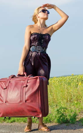 Woman in a summer outfit carrying large luggage stands at the side of a country road looking into the distance photo