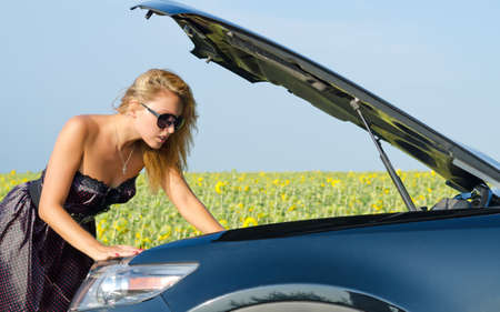 Beautiful woman leaning over with her hand in the engine compartment looking at her car engine near a field of sunflowers photo