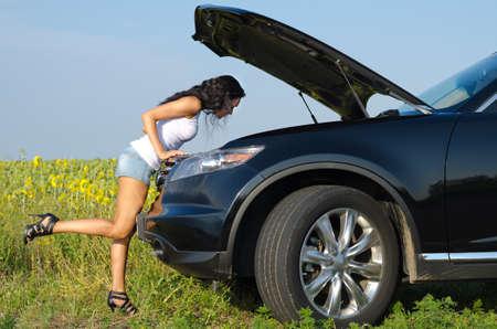 Vrouw in sexy korte broek en stilettoes leunt over het controleren van haar auto motor na het afbreken van het platteland