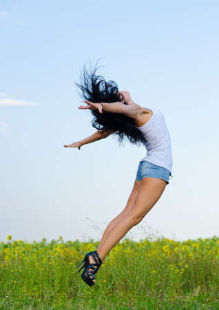 Woman in stilettoes jumping for joy in a graceful curved motion with her arms outspread photo