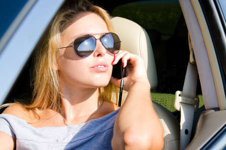 View through the open side window of a beautiful woman in sunglasses using a mobile in her car photo