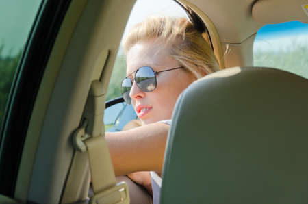View from the back seat of a woman wearing sunglasses in the front looking out of a car window Stock Photo