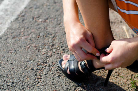 heel strap: Close up view of a woman tightening the strap on her sandal on the side of a tarred road