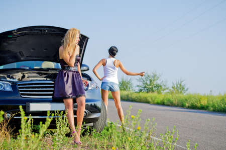 Women hitchhiking after a breakdown with their car pulled to the side of a country road with the hood up photo