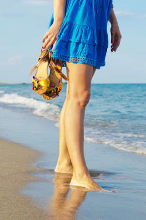 Woman holding her sandals in her hands while standing in wet sand at the edge of the surf on a beach