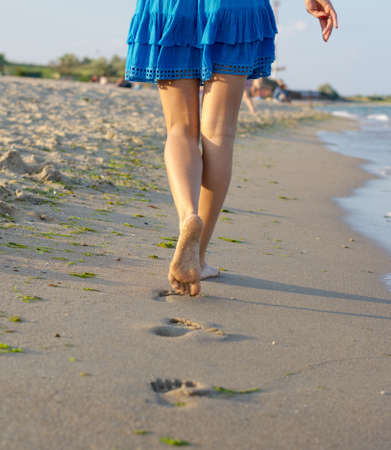 The legs of a barefoot woman walking away from the camera across wet sand on a beach leaving a line of footprints