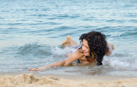 frolicking: Beautiful brunette woman frolicking in the shallow surf on a tropical beach