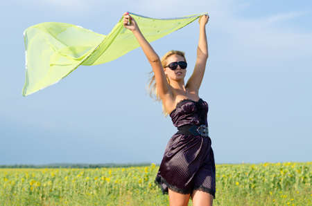 Trendy young woman in a stylish dress and sunglasses with her scarf fluttering in the breeze above her head in a counrty field photo