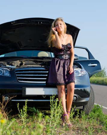 Modieuze jonge vrouw bellen om hulp op haar mobiele terwijl ze leunt tegen haar auto die is afgebroken in de natuur Stockfoto