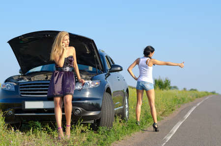 Women with a roadside breakdown telephoning for assistance and standing with a thumb out hitchhiking photo