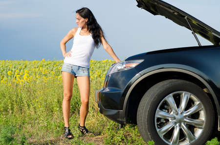 Beautiful woman in sexy shorts standing in front of the bonnet of a broken down car in the countryside photo