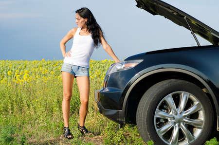 Mooie vrouw in sexy borrels staan voor de motorkap van een kapotte auto op het platteland