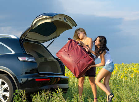 Two women tourists loading a heavy bag into the back of an estate car with the boot open near a field of sunflowers Archivio Fotografico