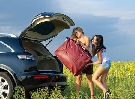 Twee vrouwen toeristen het laden van een zware tas op de achterkant van een stationcar met geopende achterklep de buurt van een veld van zonnebloemen