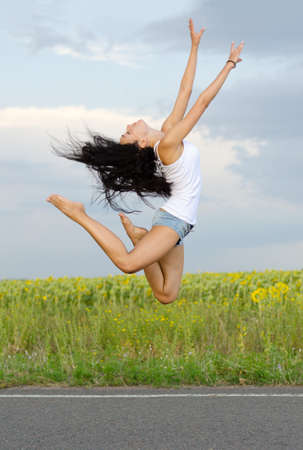 Graceful ballerina leaping high in the air on a tarred country road with her arms extended to the sky photo