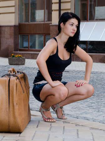cuclillas: Tur�stico hermoso de la mujer en cuclillas al lado de una gran maleta esperando un ascensor