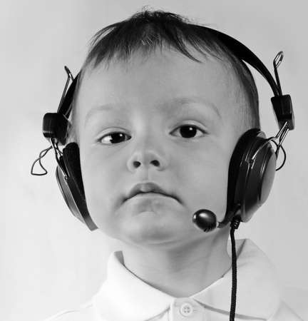 serious little boy in ear-phones with a microphone in call center answers a call on a white background