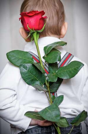 De kleine jongen heeft een verrassing voor mamma, de bloem van een rode roos en houdt het achter de rug