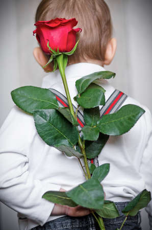 The little boy has prepared a surprise for mum, the flower a red rose and holds it behind the back
