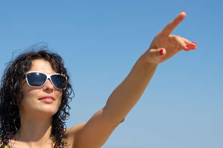Beautiful brunette woman in sunglasses pointing with her finger up into the blue sky photo