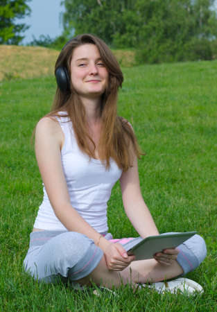 Happy young woman listening to music sitting cross legged on the grass with her tablet in her hands photo