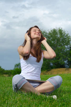 Girl sitting crosslegged on green grass looking up towards the sky with her eyes closed in enjoyment listening to music on headphones photo