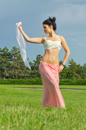 Beautiful woman in a long skirt with bare midriff dancing with a scarf on a green lawn in the garden