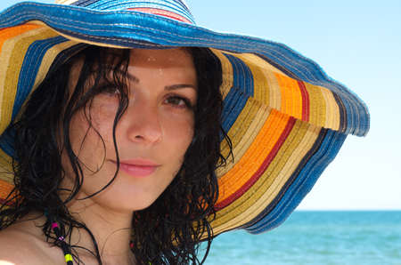 Beautiful brunette woman wearing a wide brimmed colourful sunhat at the seaside for protection from the ultraviolet rays of the sun Stock Photo - 14977577