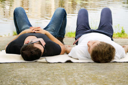Two guys relaxing together lying in their jeans on a blanket alongside a river or lake