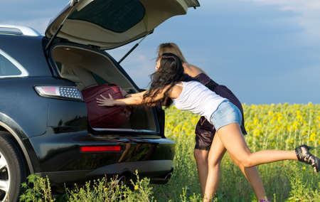 Two women loading luggage into the back of an estate vehicle parked alongside the road in the countryside near a field of sunflowers Stock Photo - 15277436