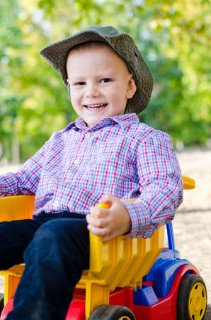Happy little boy with a big smile on his face sitting in the load bin of a colourful toy truck Stock Photo - 15277441