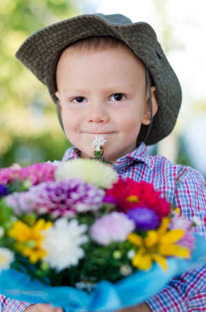 Little boy in a hat with a large bunch of colourful flowers for Mum on Mothers Day Stock Photo - 15277435