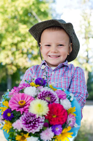 Beaming little boy with a colourful bouquet of giftwrapped flowers for his mother or sweetheart on Valentines day Stock Photo - 15277431