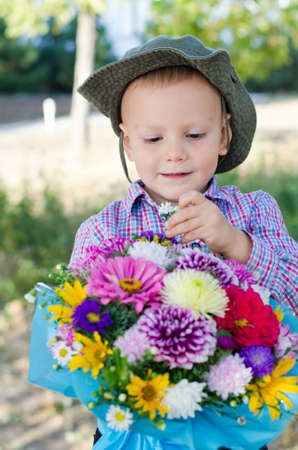 Little boy carefully removing a single flower from a large colourful giftwrapped bouquet that he is holding Stock Photo - 15277423