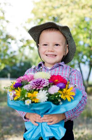 Sonriendo chico joven con un ramo de flores envuelto en papel azul colorido de pie en el bosque Foto de archivo - 15277424